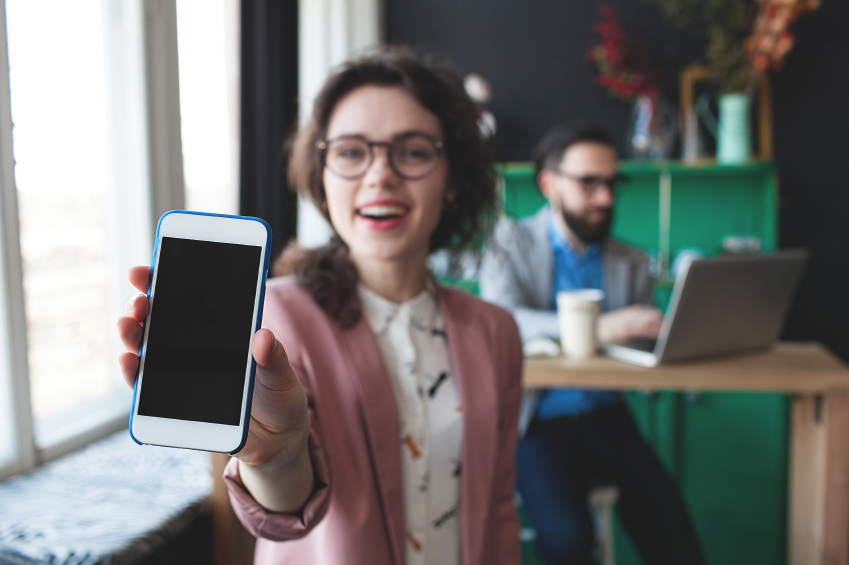 Woman in glasses showing smartphone and businessman working on b